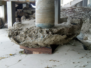 I think I'd be just a bit worried if the foundation of my multi-million dollar beach-front home was as laid bare and undermined as this. Wave action has removed all the supporting sand from around the footing of this home's pier, exposing the wood piling underneath.