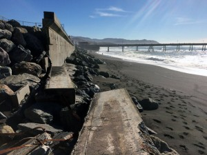 Broken seawall, with the Pacifica Pier in the distance.
